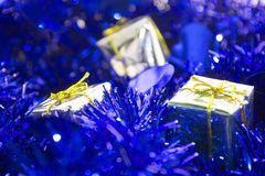 Christmas decorations, shiny and blue. Silver packs on a blue glossy surface Royalty Free Stock Photos