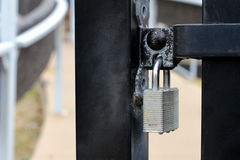 Silver padlock on black wrought-iron metal gate with blurred background. A silver padlock is locked on a black wrought-iron metal gate with peeling paint.   The Stock Photography