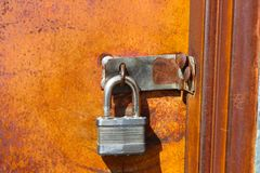 Silver padlock on old rusty door left unlocked where anyone can get in - vibrant colors of orange and brown rust. A Silver padlock on old rusty door left Royalty Free Stock Photo