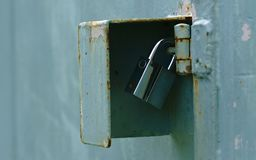 Silver padlock securing corrosive light blue door hinge. Close up view of silver padlock securing corrosive light blue door hinge royalty free stock photos