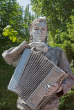 Silver painted artist with accordion dressed as Russian Soviet soldier of World War II on a city street Stock Photo