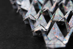 Silver paper birds. Rows of silver paper cranes facing the same direction. Shallow depth of field Stock Photography