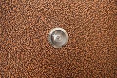Silver peephole in brown iron door Stock Photos