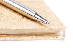 Silver pen. On brown notebook Stock Photo