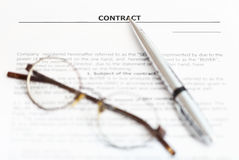Silver pen and eyeglasses on sales agreement Stock Photos