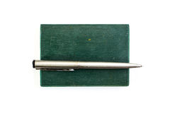 Silver pen and green notebook Stock Image