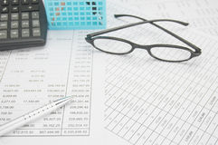 Silver pen have spectacles and calculator with blue pencil basket Stock Photo