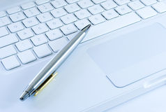 Silver pen on a laptop keyboard Stock Photography