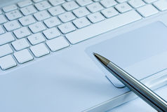 Silver pen on a laptop keyboard Stock Photo