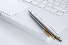 Silver pen on a laptop keyboard Royalty Free Stock Photography