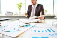 Silver pen lie at important paper on table in office. Closeup with businessman in background. Paperwork job trade balance bank credit loan money invest payment royalty free stock photo