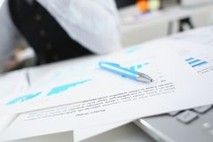 Silver pen lying on important paper at table. With people in background in office closeup. Trade result form paperwork job bank credit loan balance invest Royalty Free Stock Photo
