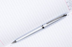 Silver pen on notebook Royalty Free Stock Photo