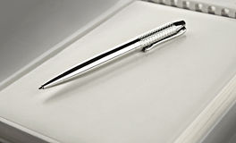 Silver pen on notebook Royalty Free Stock Images