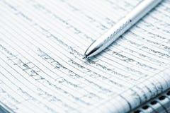 A silver pen on a notebook - blue toned image Stock Photos