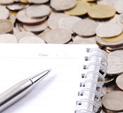 Silver pen on notebook. With coins background Stock Photos