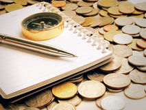 silver pen on notebook with coins background, warm tone Royalty Free Stock Image