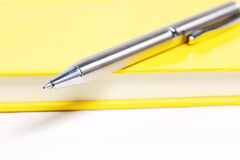 Silver pen. On yellow notebook Stock Photography