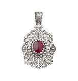 Silver pendant decorated by red gemstone Royalty Free Stock Images