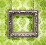 Silver picture frame hung against floral wallpaper Stock Photo