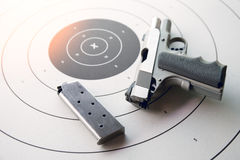 Silver .45 pistol with magazine on bullseye target Royalty Free Stock Photography