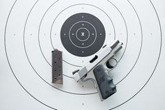 Silver .45 pistol with magazine on bullseye target Stock Photos