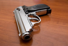 Silver pistol on a table Royalty Free Stock Image