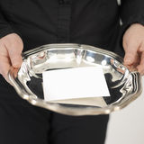 Silver plate. Female butler offering a busness card om a silver plate  (copy space Royalty Free Stock Photography