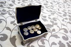 Silver plated box with silver wedding coins with the lid open on a white mat with prints on plants royalty free stock image