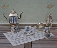 English tea set, silver-plated teapot, spoon vase and teaspoon, sugar bowl and metronome for music on a sheet of music stock images