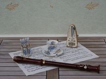 English teacup and saucer spoon vase, teaspoon, with floral decor, and metronome for music and a block flute on a sheet of music royalty free stock photo