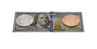 Silver and platinum coin Bitcoin lies on a hundred dollar bill. On the bill a hundred dollars are two coins of Bitcoin, silver and platinum Stock Photo