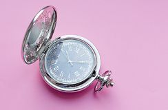 Silver pocket watch with Arabic. Pocket watch on a pink background royalty free stock photography
