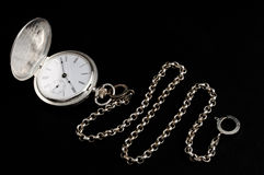 Silver pocket watch with chain. Elegant carved silver pocket watch with chain isolated on black Stock Photography
