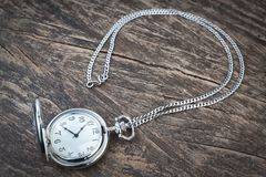 Silver pocket watch on chain, a wooden texture. Royalty Free Stock Photo