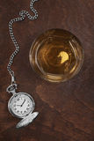 Silver pocket watch. And a glass of whiskey Stock Image