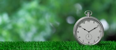 Pocket watch isolated on green grass and green abstract background, copy space. 3d illustration. Silver pocket watch isolated on green grass and green abstract vector illustration