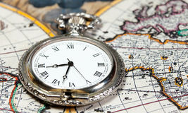 Silver pocket watch over old world map. Vintage big silver pocket watch  with antique world atlas on the background Stock Photography