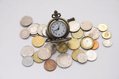 Silver pocket watch putting on various sizes coin stack with whi Royalty Free Stock Photo