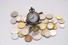 Silver pocket watch putting on various sizes coin stack with whi Royalty Free Stock Photography