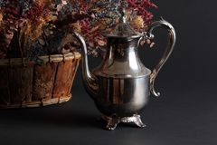 Silver Pot and Dried Flowers. Tarnished silver plated coffee pot with handle and lid plus woven basket of dried flowers on a black background Stock Photos