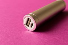 Silver powerbank on purple background. The concept of electronic royalty free stock image