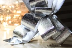 Silver present bow and beautiful lights on the back. Decoration elements perfect for christmas and new year cards royalty free stock image