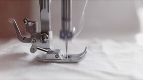 The silver presser foot of the sewing machine presses the fabric and stitches it with a needle. The notched rail. Advances the fabric while the sewing machine stock video