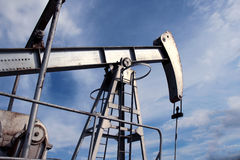 Silver pumpjack in crude oil field mine. Under sky Stock Photos