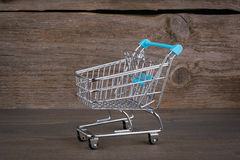 Silver Purchasing cart on a dark wooden background royalty free stock image