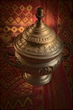 Silver pyxis. On a oriental fabric background Stock Photos