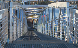 Silver Ramp to floating dock. A bright shiny ramp leads down to a float dock Royalty Free Stock Photos