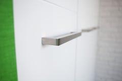 Silver rectangular haft. Detail of white closet with silver rectangular haft Royalty Free Stock Photos