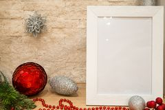 Silver and red christmas balls decoration, christmas mock up frame, silver snowflake, red beads and red winter berries with fir t. Ree branch on brick wall royalty free stock photos